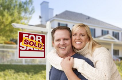 33420961 - affectionate happy couple in front of new house and sold for sale real estate sign.