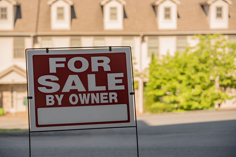 Blank For Sale By Owner Sign In Front Of A Row Of Town Houses Or